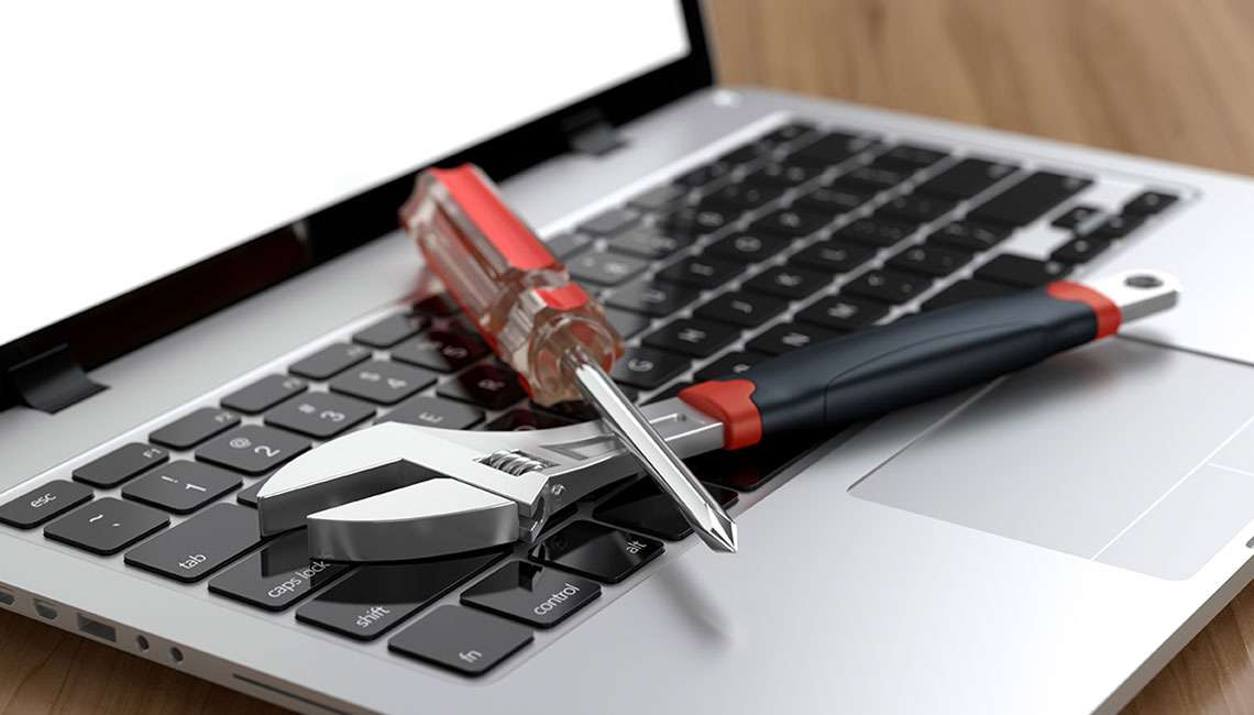 Laptop with spanner and screwdriver on keyboard