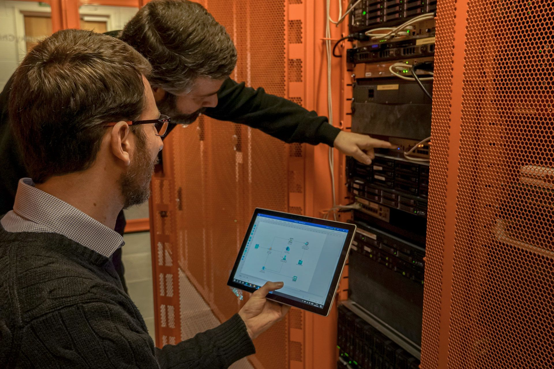 two colleagues working on servers - one holding tablet - one pressing button on server