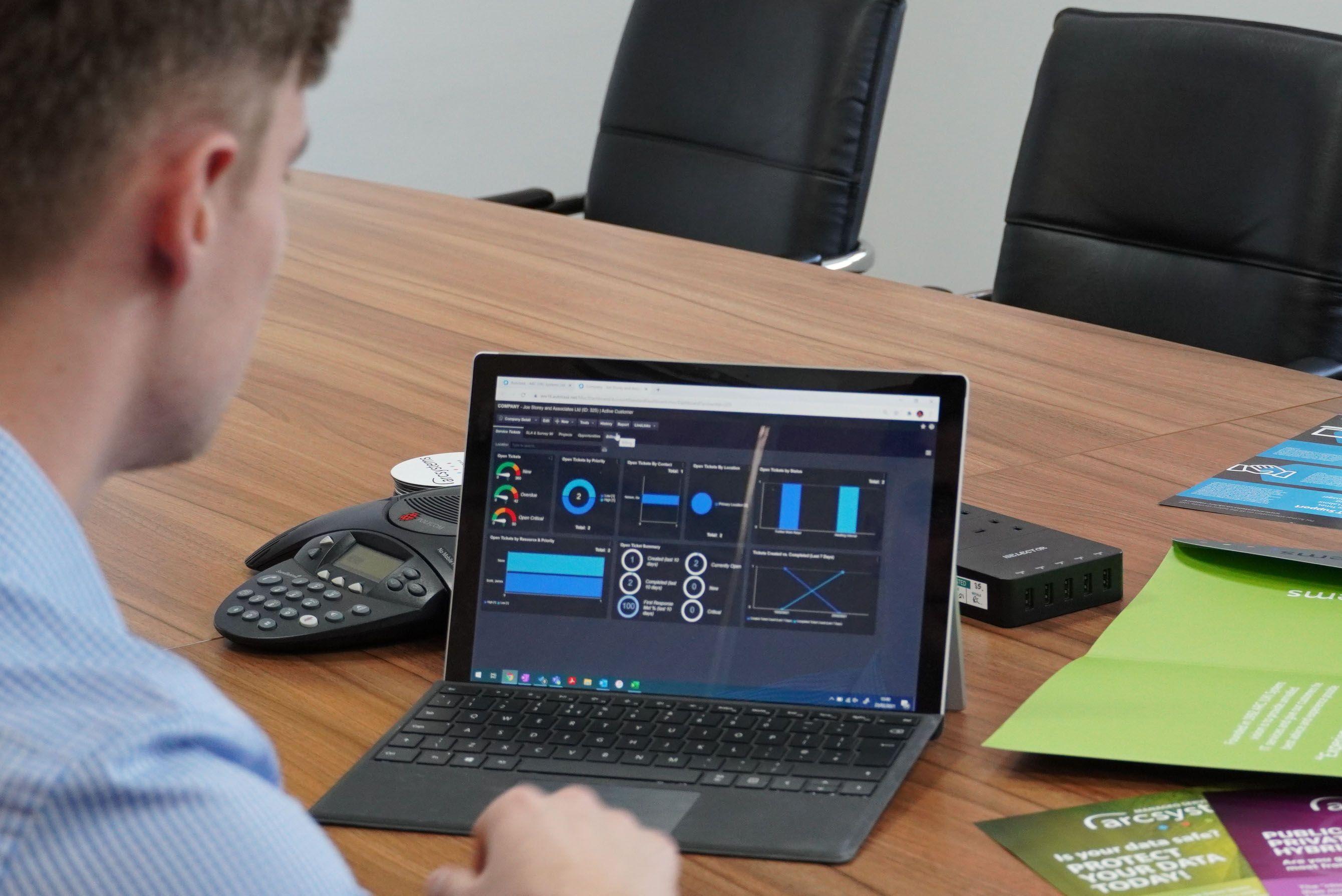 man at desk working on laptop displaying analytics data
